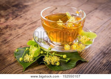 Green herbal tea with linden flowers and leafs on old wooden table