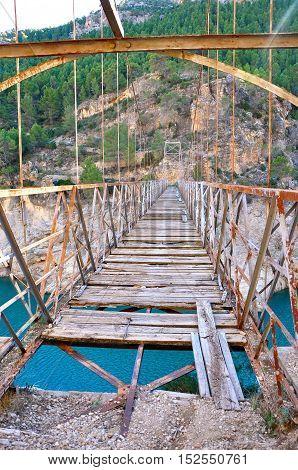 Old iron bridge and wood closed to step over the river in Yeste Albacete Spain