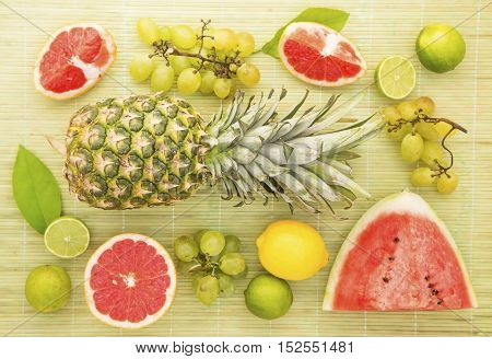 Fresh fruits on a gray straw background