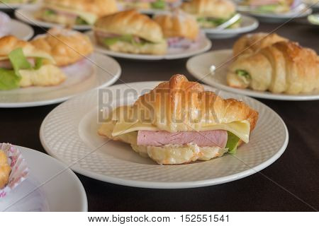 Croissant ham cheese on white plate for serving