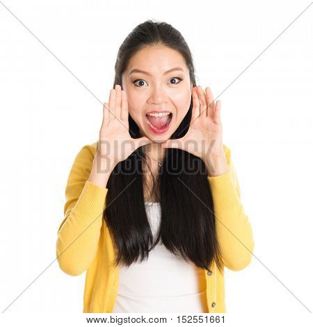 Portrait of Asian girl, shouting and looking at camera, standing isolated on white background.