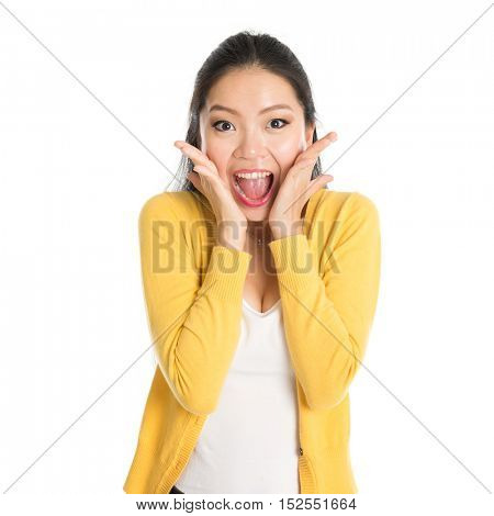 Shocked Asian woman mouth open wide, shouting and looking at camera, standing isolated on white background.