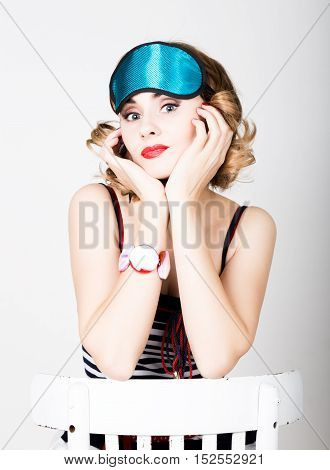 beautiful young woman in a striped dress and points for sleep, sitting on a chair and posing. sleeping eye covering mask.