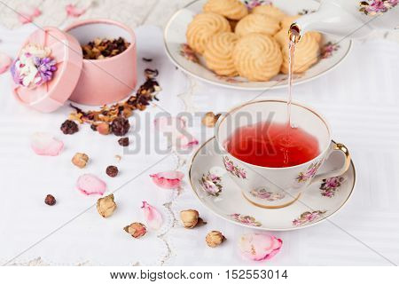 cup of red tea and biscuits on white serving table