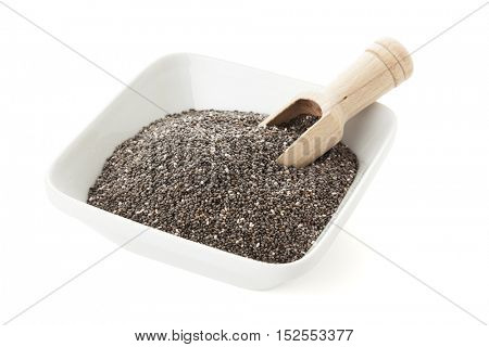 Bowl of Chia seeds with wooden shovel isolated on white background