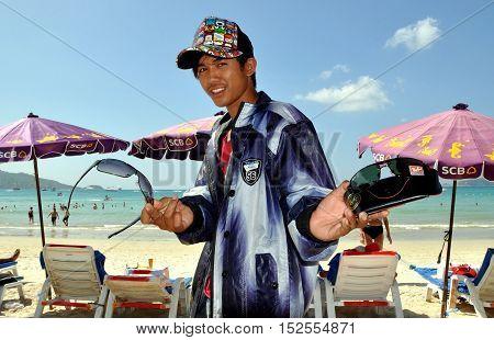 Phuket Thailand - January 6 2012: Thai youth peddling sunglasses walking along Patong Beach seeking customers