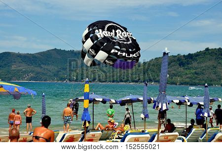 Phuket Thailand - January 11 2011: Beach goers watch a paraglider chute as it prepares to lift off from Patong Beach