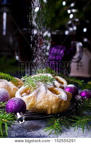 Puff with jam sprinkled with powdered sugar on the background of Christmas decorations. Selective focus.