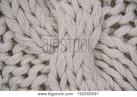 Macro flat view of knitted undyed wool surface with braid