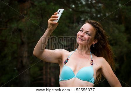 Girl In Bathing Suit In The Forest And Cell Phone