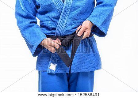 Athlete's hands, Judo, tie a black belt around the body.