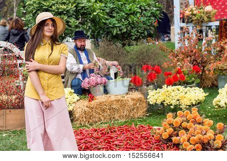 TBILISI, GEORGIA - OCT 16, 2016: Cute young woman in romantic hat walking at harvest garden of the festival Tbilisoba on October 16, 2016. Tbilisoba is traditional festival in capital of Georgia from 1979