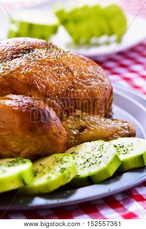 closeup of an appetizing roast turkey in a tray with vegetables, on a table set with a red and white checkered tablecloth