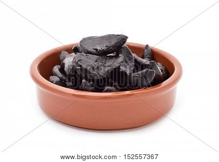 some black garlics in an earthenware bowl on a white background