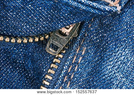 Macro flat view of blue denim jeans details with zipper