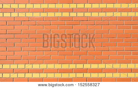 A fragment of a wall of red and yellow brick in the background