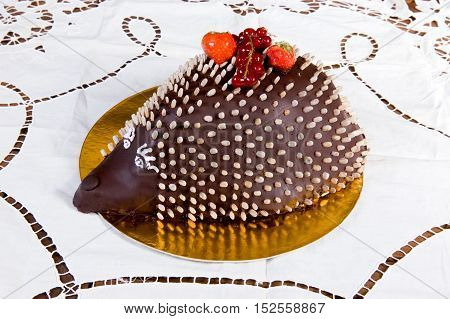 Cake in the form of a hedgehog adorned with berries on a plate background