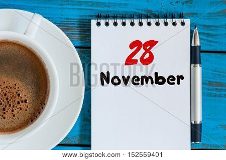 November 28th. Day 28 of month, morning coffee cup with calendar on financial adviser workplace background. Autumn time.