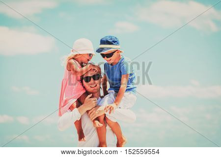 appy father with two kids on shoulders at sky, happy family