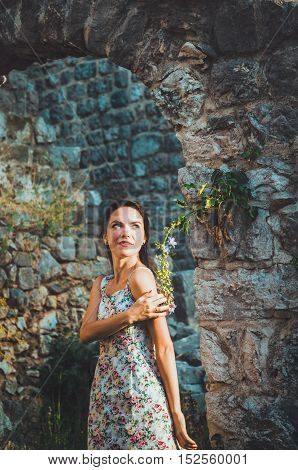 Feminine romantic woman posing in Stari Bar old fortress, Montenegro. Tanned female with long hair, red lips and manicure in white dress flowers. Brunette girl walks around oldest castle