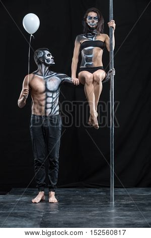 Strong couple of pole dancers in the dark studio. Man holds a pylon with the left hand and holds a balloon in the right. Girl sits on the guy's left arm. They have a horrific body-art. Vertical.
