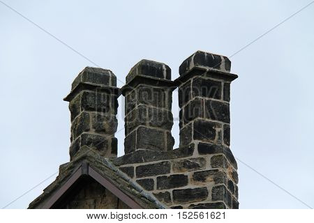 A Set of Three Stone Chimneys on a Rural Cottage.