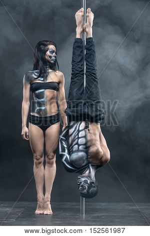 Fabulous couple of pole dancers with a horrific body-art in the dark studio with a cloud of a smoke. Man hangs upside down on a pylon. Girl stands on her toes next to him. Vertical.