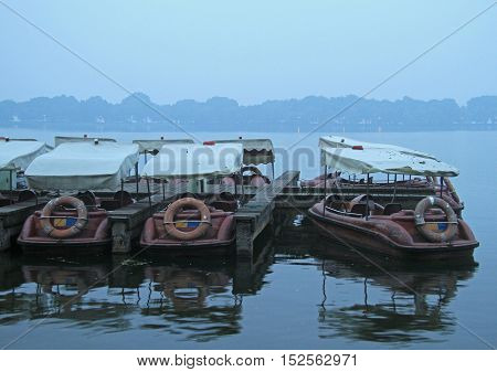 Chinese recreation boats are moored on the West Lake coast. Famous park in Hangzhou city China