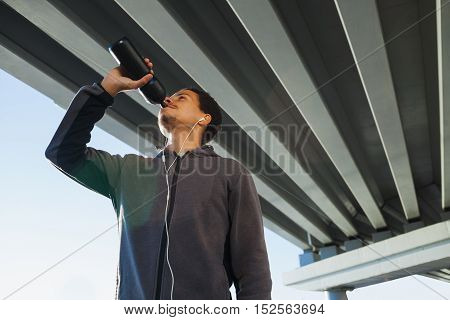 Athletic man drinking water in the city