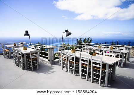 Luxury terrace balcony of exclusive restaurant with retro table and chairs and full sea panorama from the top of the mountain in Greek island Lefkada
