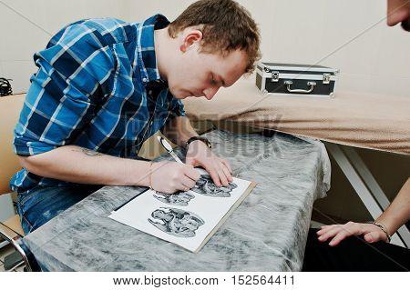 Tattoo master preparing sketch for tattoo at saloon