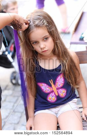 a college student working as outdoor vendor braiding little girl's hair in summer time