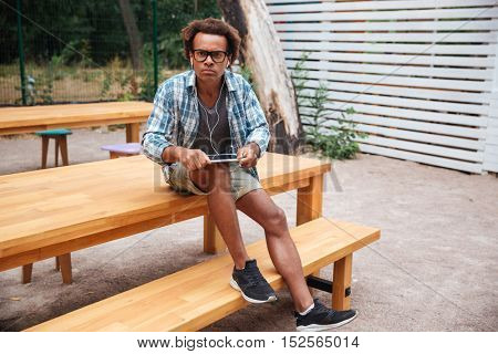 Angry african young man in glasses using tablet with earphones outdoors