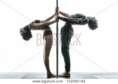 Beautiful couple of pole dancers with horrific body-art stands next to a pylon in the studio on the white background. They are holding their hands on the pylon and tilting their bodies backward.