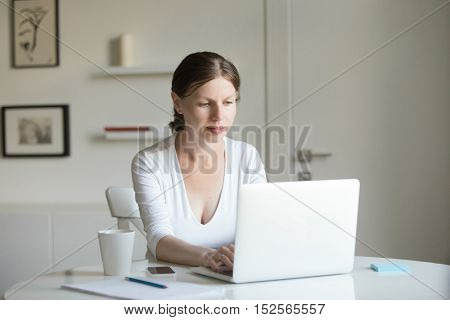Portrait Of Young Attractive Woman At The Desk With A Laptop