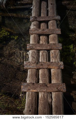Narrow and ruined small wooden bridge at Black river gorge, Altai