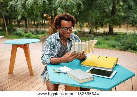 Happy handsome young man in glasses reading and sudying in outdoor cafe