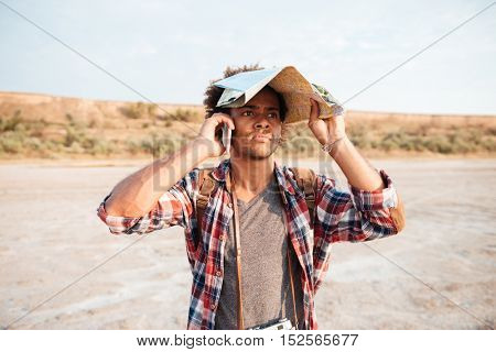 Serious african young man covered head with map and talking on mobile phone outdoors