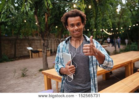 Happy african young man in earphones holding tablet and showing thumbs up