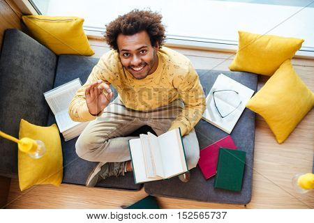 Top view of happy african american young man reading book and showing ok sign at home