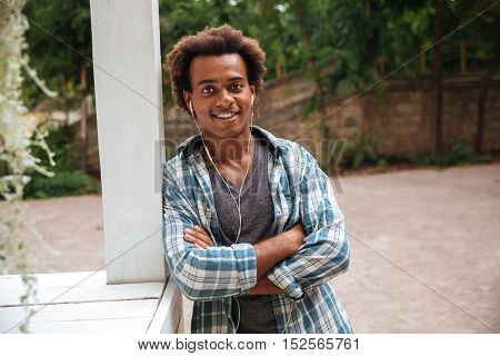 Smiling handsome african young man in earphones standing with arms crossed