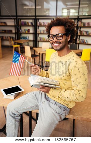 Cheerful african young man with flag of United States reading book in library