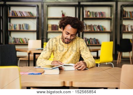 Concentrated african american young man reading book and learning in library