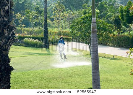 Worker is watering the grass in the golf course.