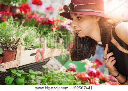 Beautiful young woman smelling flowers in a flowers shop