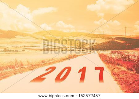 new year 2017 written on rural road countryside warm filter applied