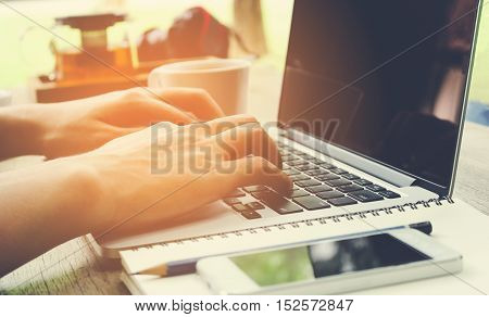 Man hand use laptop working with mobile phone vintage tone.