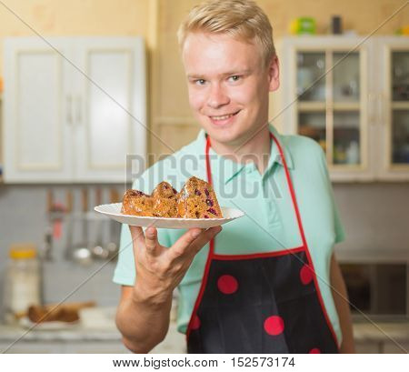 Smiling young male chef in an apron holding a cake, standing in home kitchen.
