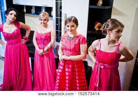 Four bridesmaid at room in pink dresses
