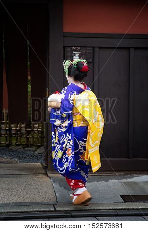 KYOTO, JAPAN - 15th June 2016: Geisha in full costume and make-up, enters a house in Gion, Kyoto, Japan.